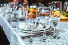 Bordlägga inställningen med exponeringsglas, plattor, servetter och mat Arkivbilder