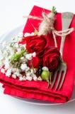 Bordlägga inställningen med röda ro, servetter och tappningcrockery Arkivbild