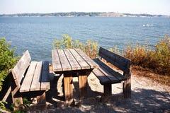 Bordlägga och bänkar på kusten av golfen av Finland Arkivfoto