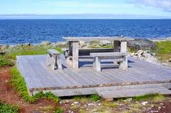 Bordlägga och bänkar vid havet på en träplattform Royaltyfria Bilder