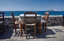 Bordlägga och den grekiska tavernaen för stolar på sjösidan Arkivbilder
