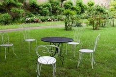 bordlägga och fyra vita stolar i trädgården Arkivbilder