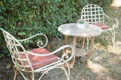 Bordlägga och stolar som står i trädgården med skuggor Arkivbild