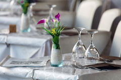 Bordlägga uppsättningen med blommor, exponeringsglas, servetter och gafflar Arkivbilder