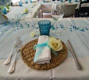 Bordlägga uppsättningen med plattor, bestick, och exponeringsglas, blått bugar och vit r Arkivbilder