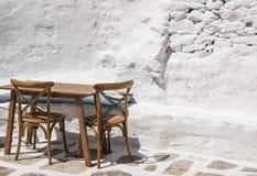 Bordlägga yttersidan mot en vit stenvägg i de grekiska öarna Arkivfoton