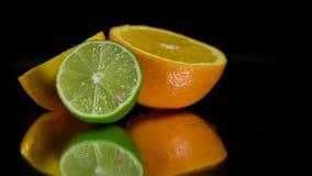 Bordlägger halvan en apelsin, en limefrukt och en citron på en spegel arkivfilmer