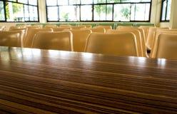 Bordlägger och stolar som inget sitter i seminariumrummet arkivfoto