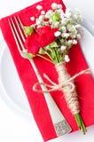 Bordlägga inställningen med röda ro, servetter och tappningcrockery Arkivfoton
