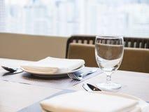 Bordlägga matställeuppsättningen med plattaservetten och exponeringsglasrestaurangbakgrund Arkivbilder