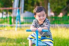 Bordo asiatico del movimento alternato di guida del bambino al campo da giuoco Fotografia Stock Libera da Diritti