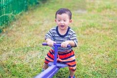 Bordo asiatico del movimento alternato di guida del bambino al campo da giuoco nell'ambito di luce solare, Fotografia Stock