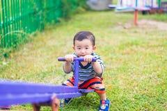 Bordo asiatico del movimento alternato di guida del bambino al campo da giuoco nell'ambito di luce solare, Immagine Stock