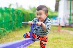 Bordo asiatico del movimento alternato di guida del bambino al campo da giuoco nell'ambito di luce solare, Immagini Stock