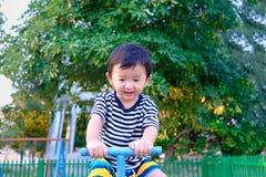 Bordo asiatico del movimento alternato di guida del bambino al campo da giuoco nell'ambito di luce solare, Immagine Stock Libera da Diritti