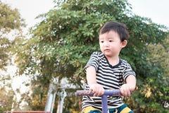 Bordo asiatico del movimento alternato di guida del bambino al campo da giuoco nell'ambito di luce solare, Fotografia Stock Libera da Diritti