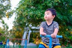 Bordo asiatico del movimento alternato di guida del bambino al campo da giuoco nell'ambito di luce solare, Immagini Stock Libere da Diritti
