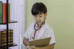 Bordo asiatico sveglio della tenuta di medico del ragazzino, analizzare i dati pazienti immagini stock libere da diritti