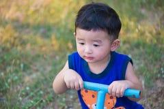 Bordo asiatico triste del movimento alternato di guida del bambino al campo da giuoco nell'ambito di sunlig Immagini Stock Libere da Diritti