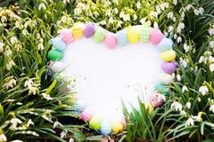 Bordo bianco con le uova di Pasqua ed i fiori fotografie stock