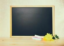 Bordo in bianco vuoto del nero della scuola con i gessi e il chrysanthem bianchi Fotografie Stock Libere da Diritti