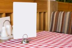 Bordo caldo dello spazio in bianco del menu sulla tavola in ristorante Fotografia Stock