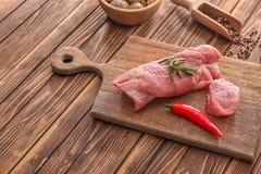 Bordo con il filetto di carne di maiale crudo sul tavolo da cucina Prodotti della carne fresca fotografie stock