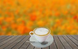 Bordo con la tazza di caffè ed il fondo della sfuocatura Fotografia Stock