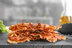 Bordo con le fette di lardo fritte del bacon su fondo vago fotografie stock libere da diritti