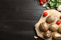 Bordo con le patate bollite con la buccia al forno saporite su fondo di legno, vista superiore immagini stock