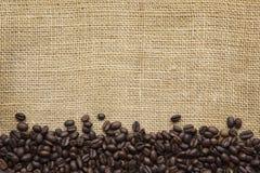 Bordo dei chicchi di caffè sopra tela da imballaggio Immagini Stock