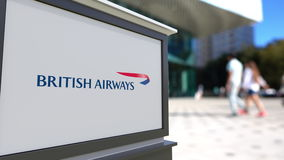 Bordo del contrassegno della via con il logo di British Airways Centro vago dell'ufficio e fondo di camminata della gente 3D edit Fotografie Stock Libere da Diritti