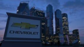 Bordo del contrassegno della via con il logo di Chevrolet nella sera Fondo vago dei grattacieli del distretto aziendale Editorial Fotografie Stock Libere da Diritti