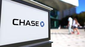 Bordo del contrassegno della via con il logo di JPMorgan Chase Bank Centro vago dell'ufficio e fondo di camminata della gente 3D  Fotografia Stock
