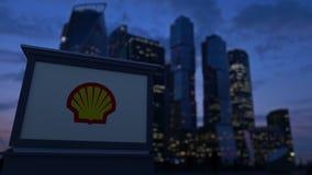 Bordo del contrassegno della via con il logo di Shell Oil Company nella sera Fondo vago dei grattacieli del distretto aziendale Immagini Stock Libere da Diritti