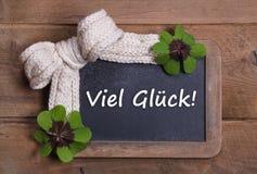 Bordo del menu con il messaggio di buona fortuna in tedesco - trifogli e bianco Immagine Stock
