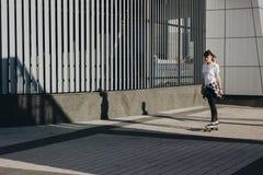 Bordo del pattino di guida della ragazza dei pantaloni a vita bassa Fotografia Stock Libera da Diritti