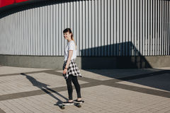 Bordo del pattino di guida della ragazza dei pantaloni a vita bassa Immagine Stock