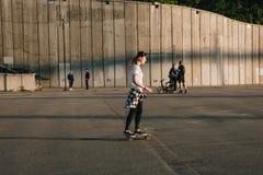 Bordo del pattino di guida della ragazza dei pantaloni a vita bassa Fotografie Stock Libere da Diritti