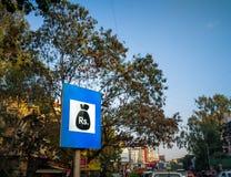 bordo del segno della banca sul bordo della strada con alcuni alberi dietro immagini stock