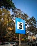 bordo del segno della banca sul bordo della strada con alcuni alberi dietro immagine stock