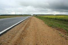 Bordo della strada largo sotto il cielo nuvoloso immagini stock