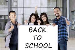 Bordo della tenuta degli studenti con di nuovo al testo di scuola Fotografia Stock Libera da Diritti