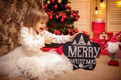 Bordo della tenuta del bambino con il Buon Natale dell'iscrizione Immagini Stock Libere da Diritti