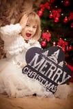 Bordo della tenuta del bambino con il Buon Natale dell'iscrizione Fotografie Stock Libere da Diritti