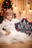 Bordo della tenuta del bambino con il Buon Natale dell'iscrizione Immagine Stock Libera da Diritti