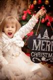 Bordo della tenuta del bambino con il Buon Natale dell'iscrizione Fotografia Stock Libera da Diritti