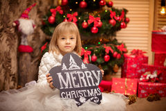 Bordo della tenuta del bambino con il Buon Natale dell'iscrizione Fotografia Stock
