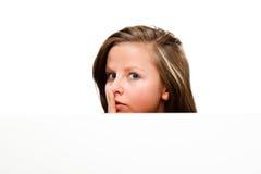 Giovane donna attraente dietro il bordo vuoto su fondo bianco Immagini Stock Libere da Diritti