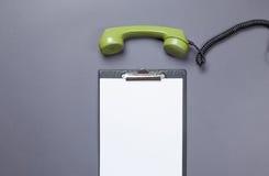 Bordo di affari e microtelefono verde fotografia stock libera da diritti
